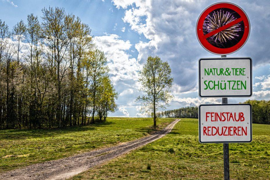 Landschaft mit Anti-Böller-Schildern zum Schutz von Natur und Tieren und Reduktion von Feinstaub